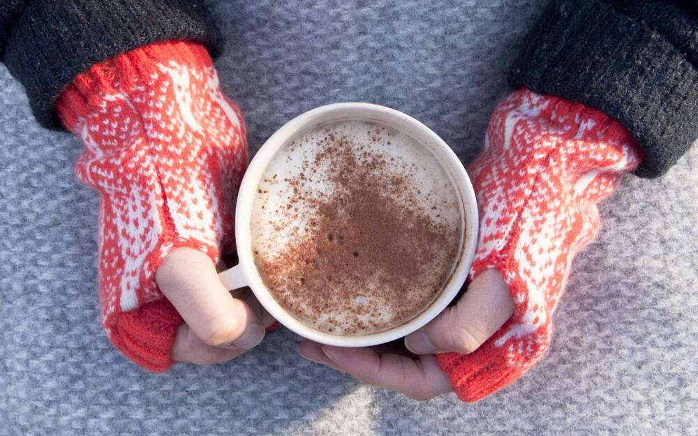 Hands With Fingerless Gloves Wred Around A Cup Of Hot Cocoa