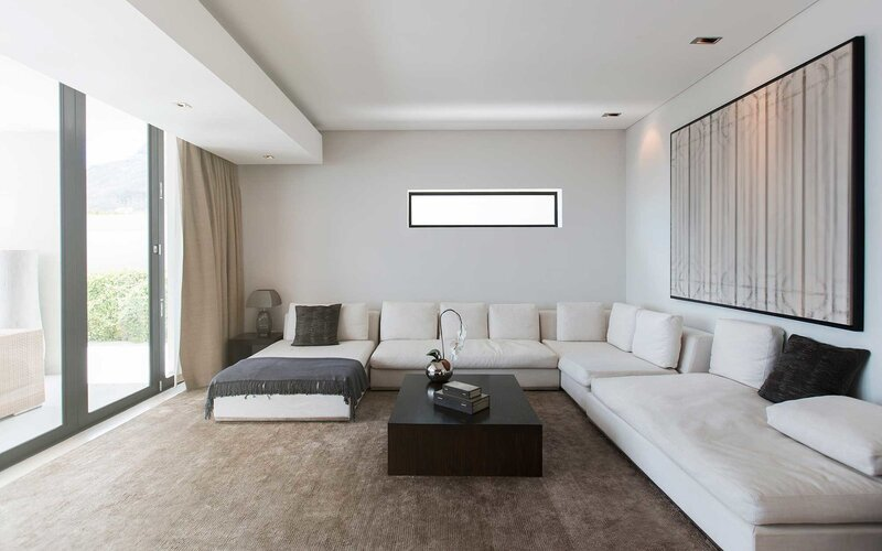View of modern living room with sofas, coffee table and abstract painting