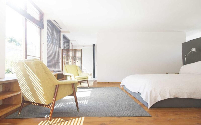 Armchairs, rug and bed in modern bedroom