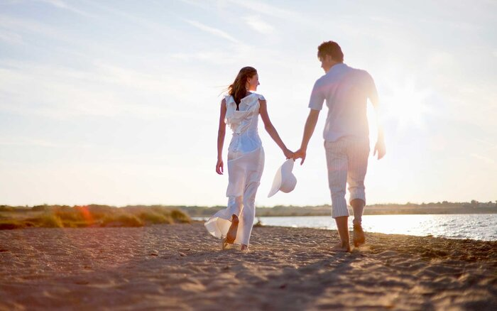 Destination wedding etiquette travel leisure newlywed couple walking on beach junglespirit