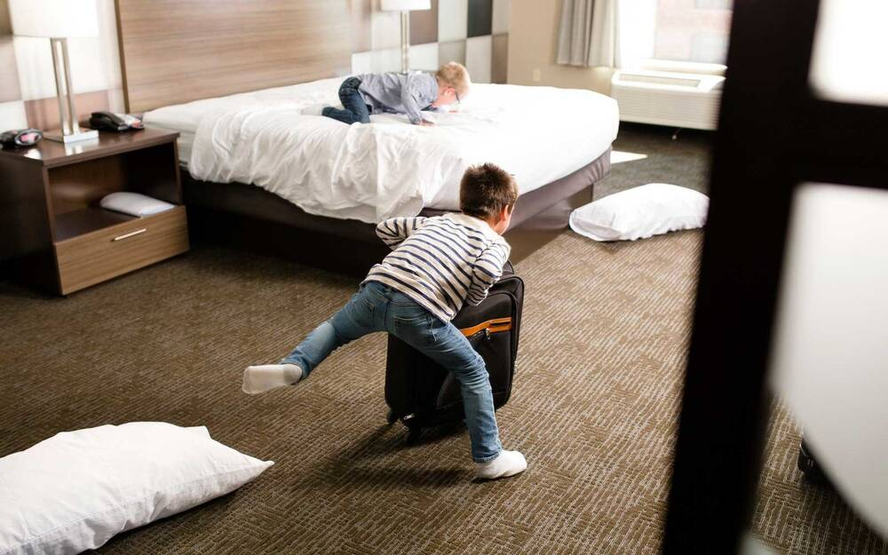 Two Boys Play In A Hotel Room