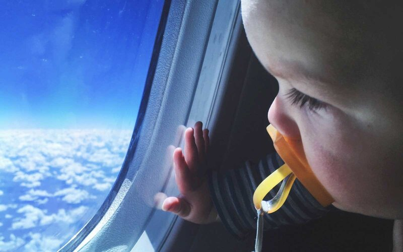 Young baby looking out of the window at the clouds below while flying in an airplane