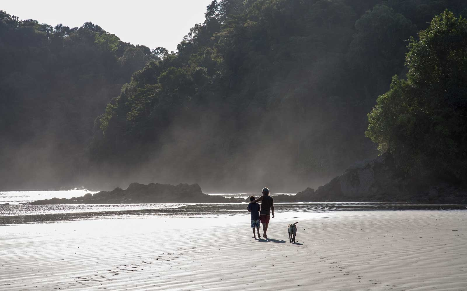 Father and son walking on the beach at sunset, Nuqui Beach, Colombia