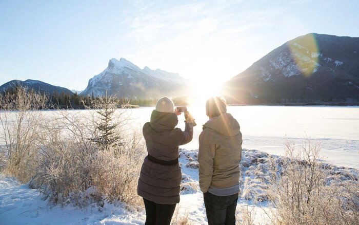 People Taking A Photo Of Frozen Lake In The Winter
