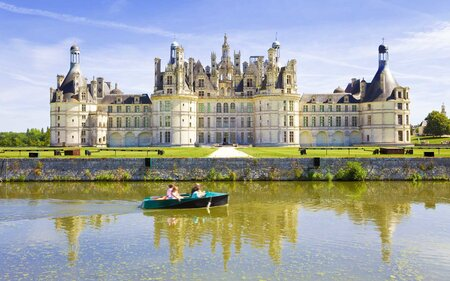 Chambord Chateau Reflected In The Canal As A Family Sails By Boat