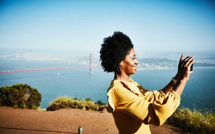 Woman Taking Photos Near Golden Gate Bridge In San Francisco