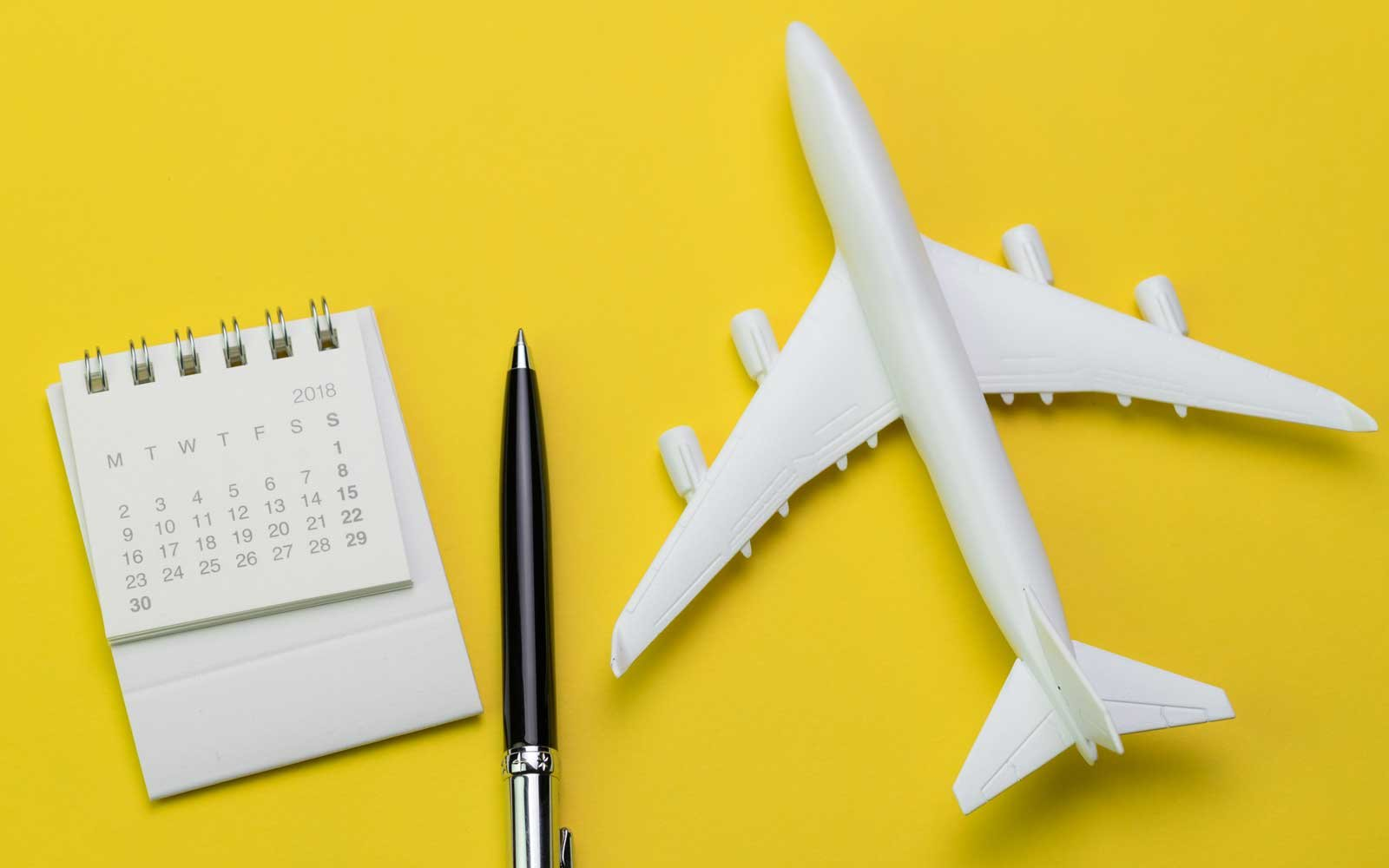 Still Life Of 2018 Calendar Pen And Toy Plane On Sunny Yellow Background