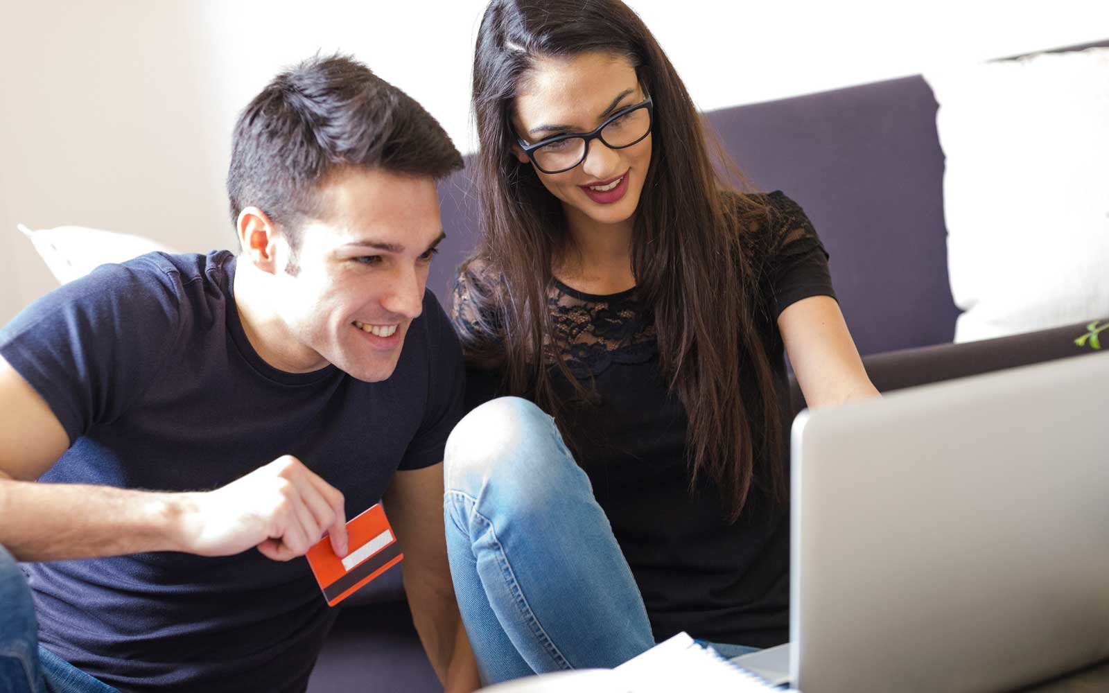 Young Couple With Credit Card Using Laptop In The Living Room
