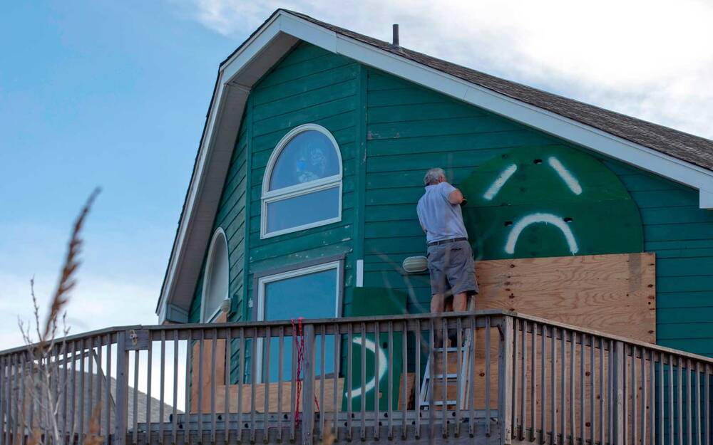 A Man Uses Drill To Install Storm Shutters On Home In Kill Devil Hills