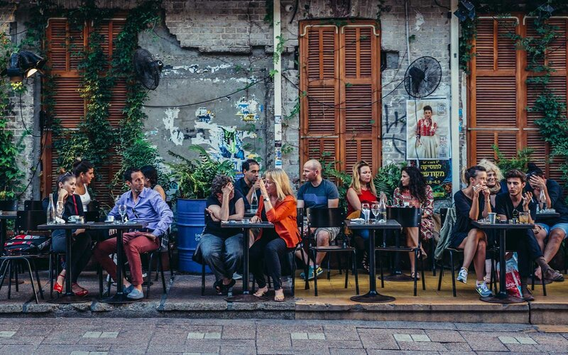 People sits at tables outside the restaurant at Rothschild Boulevard in Tel Aviv