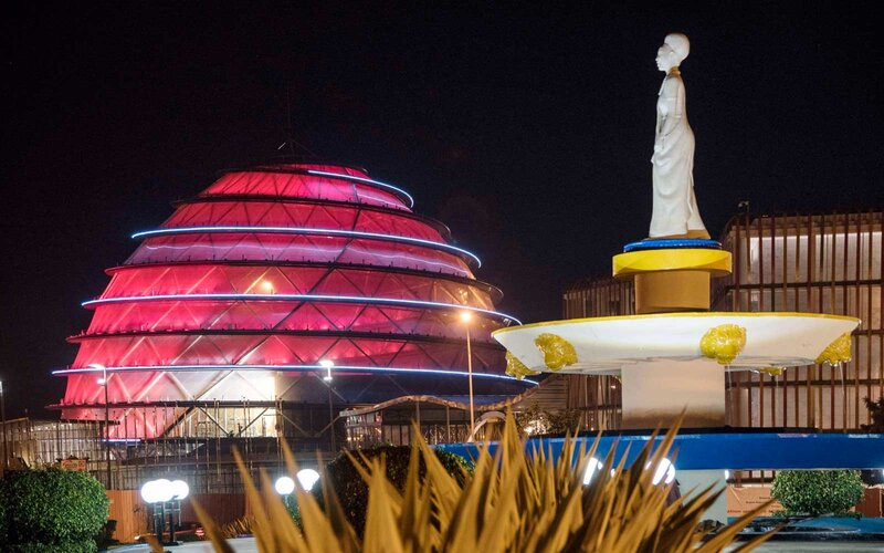 A statue honouring the strength of Rwandese women and the construction site of the Kigali Convention Centre are illuminated at night.