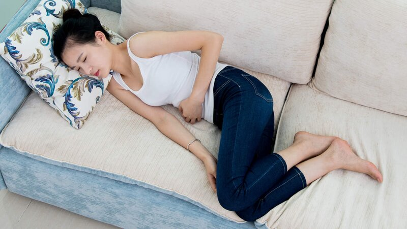 woman lying on couch clutching stomach nauseous diarrhea