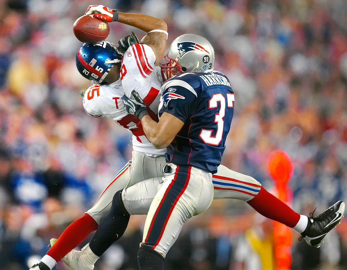 New York Giants wide receiver David Tyree somehow manages to hang on to the catch by pinning the ball against his helmet as New England Patriots safety Rodney Harrison hits him late in the fourth quarter. Tyree also caught a touchdown pass earlier in the fourth quarter that helped the Giants to their 17-14 victory.