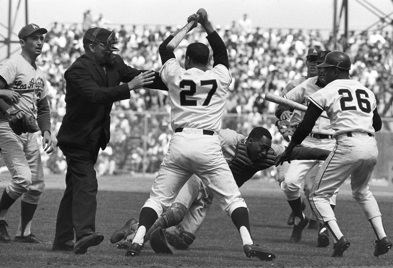 Juan Marichal hits Dodgers catcher John Roseboro with bat during a third-inning argument at Candlestick Park. Sandy Koufax (left) and Giants Tito Fuentes (26) watch NL umpire Shag Crawford attempt to stop the beating.
