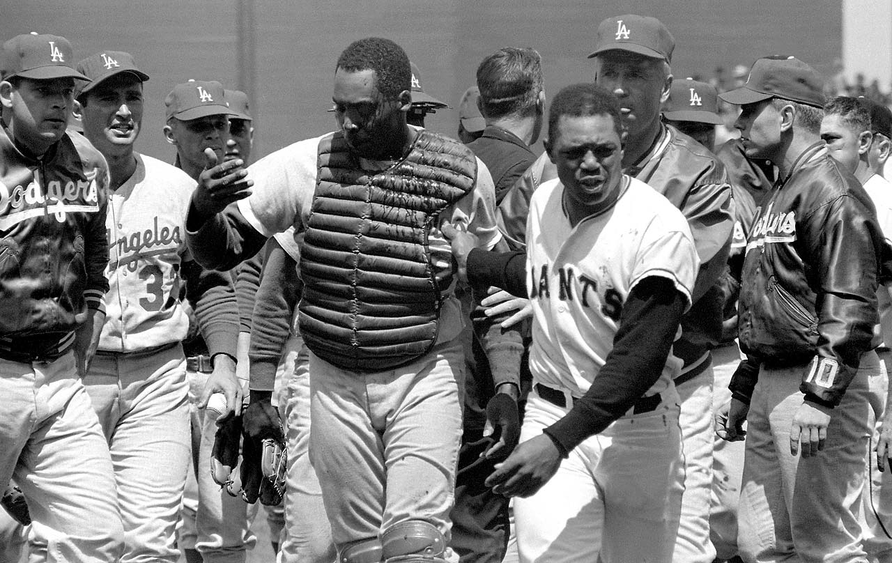 A bleeding John Roseboro walks off the field with Willie Mays as Sandy Koufax (32) watches.