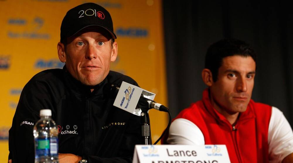 d3a17ac0e0f Lance Armstrong speaks to the media as his longtime teammate George  Hincapie listens on during a