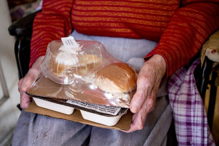 World war ii veteran serving meals on wheels southern living close up elderly hands holding packaged meal forumfinder Choice Image