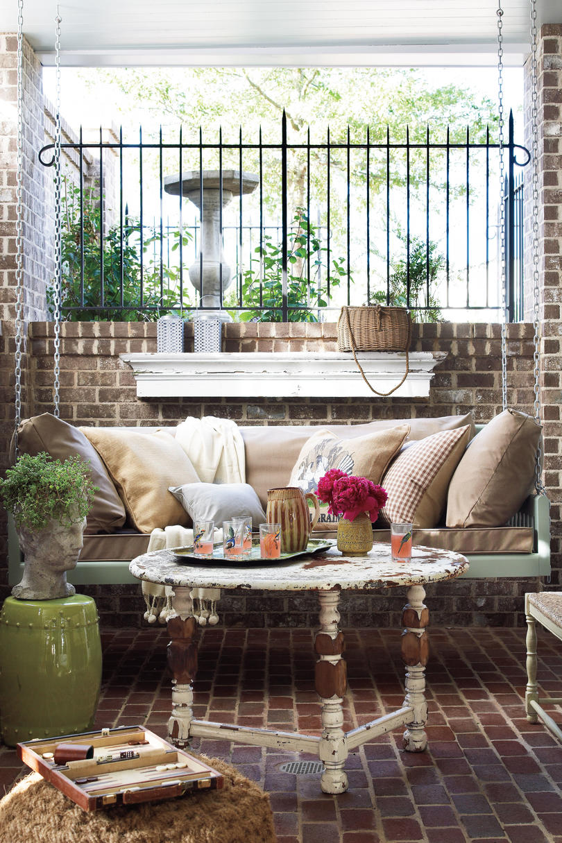 A brick porch in Georgia with charming cottage style decor and swing. #porchswing #decoratingideas #brick