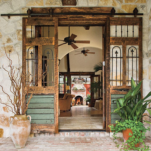 Vintage sliding doors with Southwest appeal on a rustic porch with stone wall and brick floor. #porch #rustic #decoratingideas #southwest