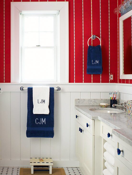Red Bathroom With White Paneling And Blue Towels