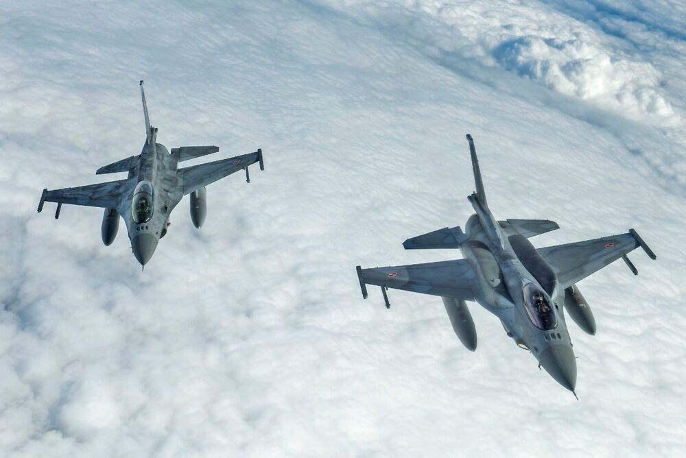 A pair of polish F-16C Block 52+ fighter jets, including one with conformal fuel tanks, fly over the Baltic Sea in June 2017.