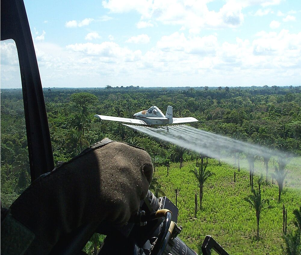 A US State Department helicopter escorts an armored crop duster on an counter-drug mission in Colombia in 2003.