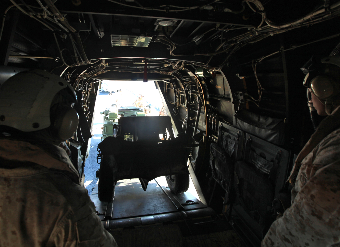 A view from inside an Osprey as Marines load an EFSS mortar system, showing the limited room to maneuver.