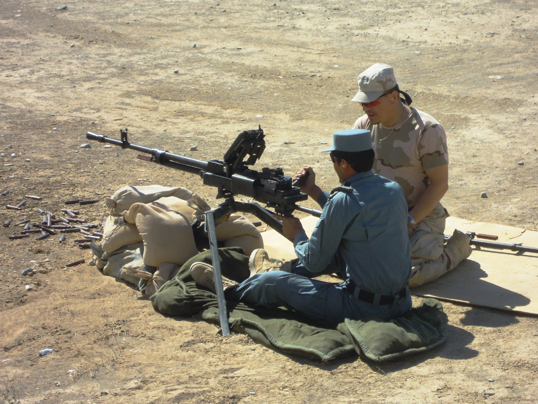 A Romanian Gendarmerie, at right, trains a member of Afghanistan's Uniformed Police to fire an NSV machine gun.