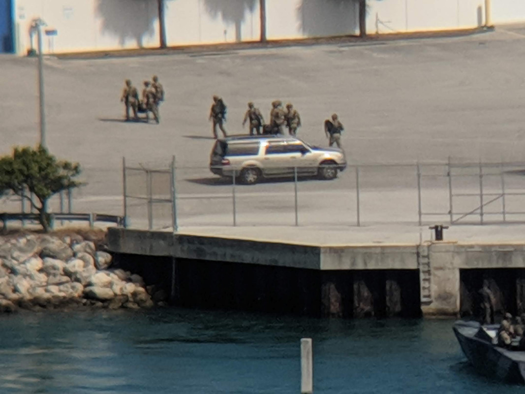 Uniformed personnel walk by an SUV on the dock.