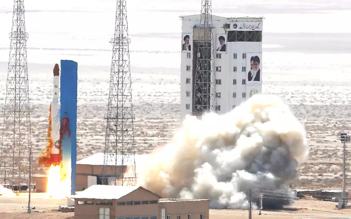 A Simorgh space launch vehicle blasts off from Semnan in 2017. The building the background is adorned with pictures of the late Ayatollah Ruhollah Khomeini and Iran's present Supreme Leader Ali Khamenei