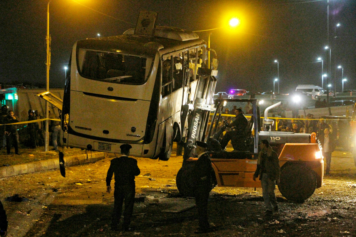 Egyptian authorities move the wreckage of a tour bus after it hit a roadside bomb outside of Cairo in December 2018.