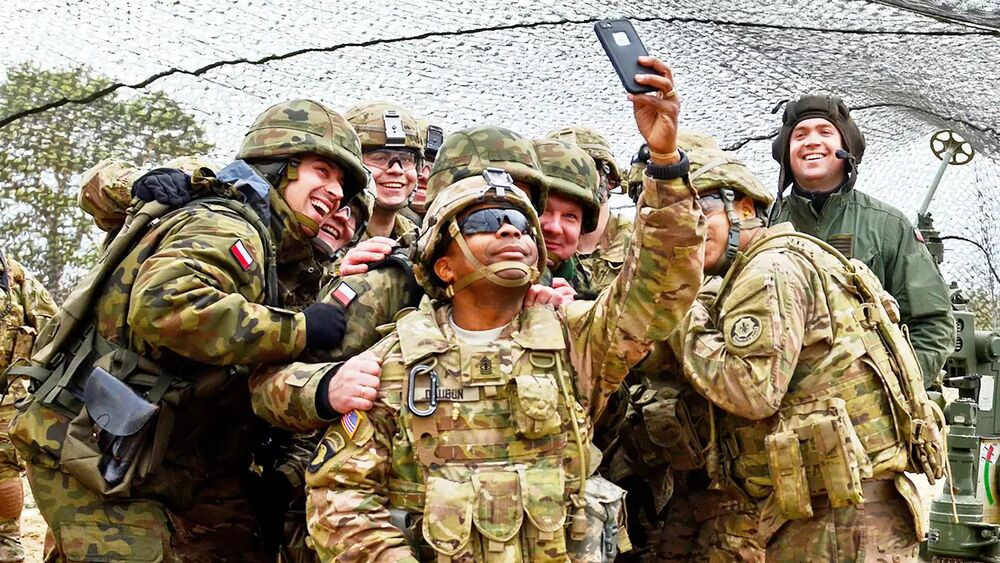 A US Army soldier takes a selfie with other American and Polish troops during an exercise in Europe.