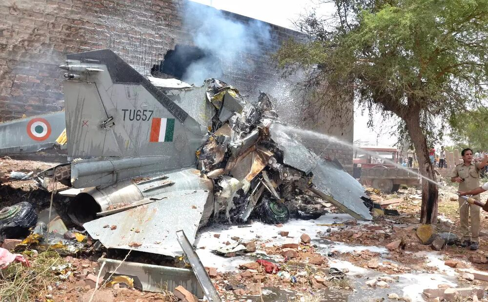 Indian firefighters hose down the remains of a MiG-27 after a crash in 2016.